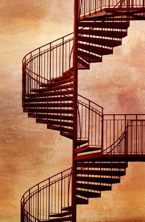 Red metal spiral staircase with grungy background.