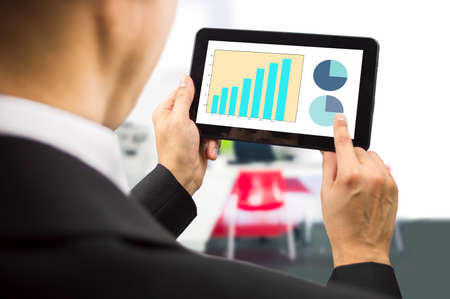 bussinesman looking at the stock market data on a tablet on the office.All screen content is designed by us and not copyrighted by others and created with tablet and ps