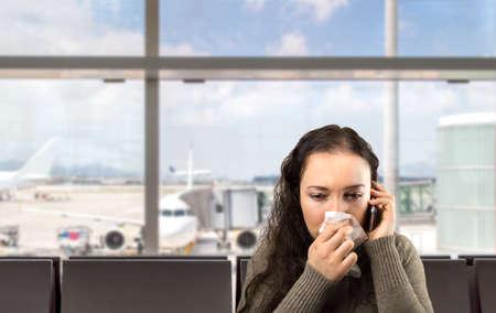 Foto de sick woman calling doctor urgently at the airport - Imagen libre de derechos