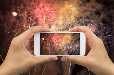 Photo pour hands of man taking the photo to fireworks with the new smartphone - image libre de droit