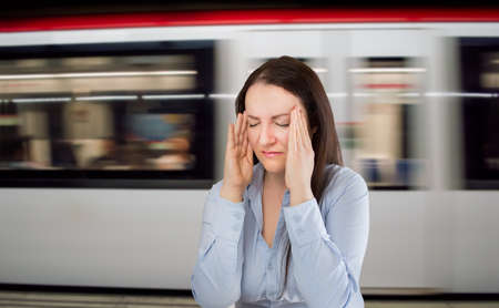 woman with headache at the underground station