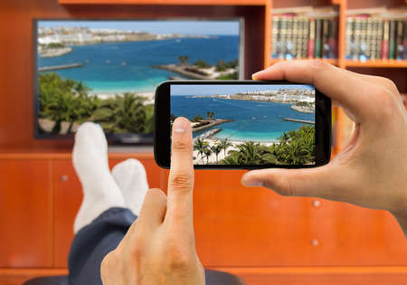 Photo pour relaxed man with smartphone connected to a tv and envisioning photos in networking (tv and telephone image from a photo of a beach at Gran canaria from my portfolio) - image libre de droit