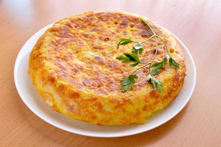 Foto de view of a spanish omelette with eggs potatoes and onion with parsley leaf on the top over a wooden table - Imagen libre de derechos