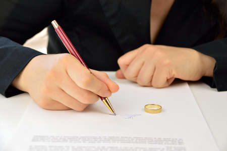 wife signing divorce agreement with the weeding ring on the contract