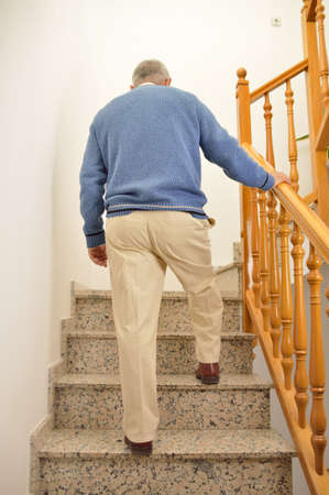 Photo pour Rear view of a mature man climbing the stairs of a house - image libre de droit