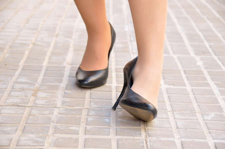 woman with twisted ankle. Female foot in pain due to sprained ankle wearing stilettos on the city sidewalk.
