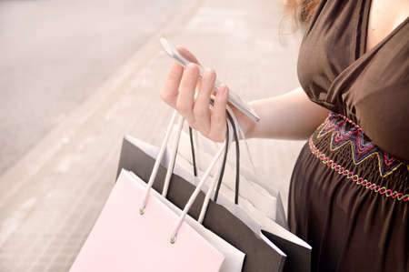 Pregnant woman shopping with a smart phone and carrying shopping bags at the  city street. Concept of a shopaholic