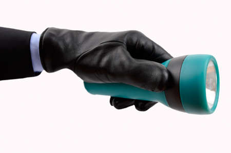hand of a thief with glove holding a flashlight looking something on a white background