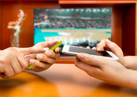 Photo for Friends using mobile phone and betting during a basketball match.With a tv background and an image of a basketball match - Royalty Free Image