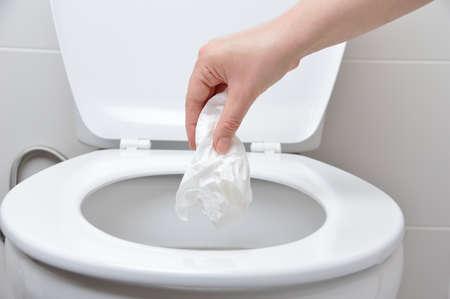 Foto de hand of a person who drop tissue paper in the toilet bowl - Imagen libre de derechos