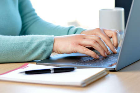 Photo pour Cropped shot of a lady hands typing in a laptop on a desk at office - image libre de droit