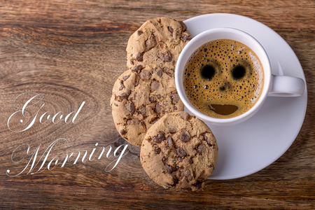 cup of coffee with chocolate cookies on wood and good morning written