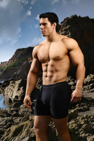 Bodybuilder on the beach with blue sky and rocks behind him