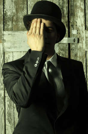 Stylized abstract portrait of a dapper man in top hat and suit covering half of his face with hand