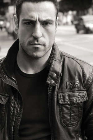Intense black and white portrait of serious looking man in leather jacket outdoors