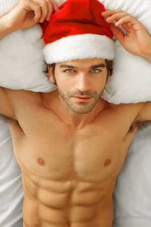 Sexy shirtless male model laying back in bed wearing Santa cap