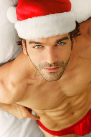 Good looking shirtless young man in Santa Claus hat and briefs in bed