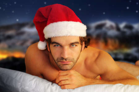 Sensual portrait of a young shirtless male model laying on pillow against fantasy winter background