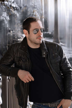 Sexy guy with attitude wearing lether jacket and sunglasses outdoors