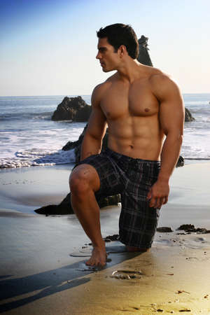Sexy young fit man on the beach looking out toward the ocean