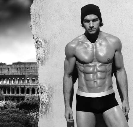 Sexy fine art black and white portrait of a very muscular shirtless maile model posing with view of Rome in the background