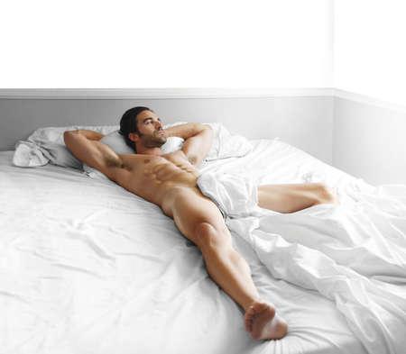 Foto de Full length portrait of a gorgeous sexy nude male model laying in bed - Imagen libre de derechos