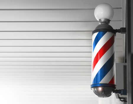 Old fashioned vintage barber shop pole against modern background