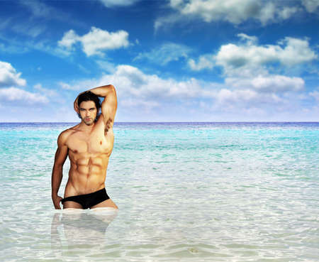 Portrait of a fit muscular male model standing in clear warm tropical waters with lots of copy space