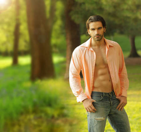 Beautiful male model with open shirt in outdoor setting