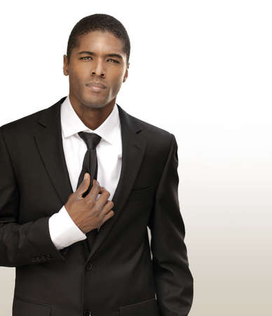 Portrait of a good looking handsome young businessman in black suit with tie against bright background with copy space