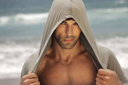 Foto de Sexy male model outdoors wearing a hooded shirt and revealing his chest - Imagen libre de derechos