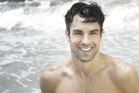 Photo pour Handsome happy man smiling with ocean water background - image libre de droit