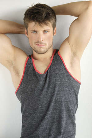 Very good looking young male model with arms up in sexy pose