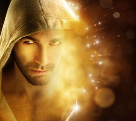 Fantastical portriat of a handsome hero type man in hooded garment in dazzling background with rays of light