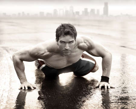 Foto de Sexy fit muscular man doing push-up on wet road with city skyline in the background - Imagen libre de derechos