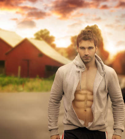 Beautiful male model with great body in romantic rustic outdoor setting with red barn in background and moody sky above