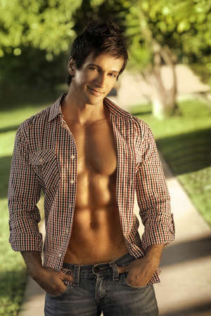 Fashion portrait of a handosme man with open shirt and muscular abs outdoors