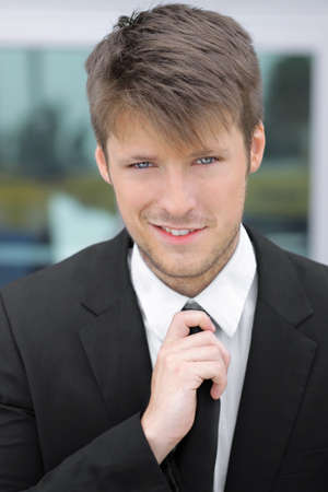 Business portrait of a happy young attractive man in suit and tie