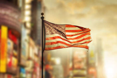 Tattered American flag blowing in the wind against cool city blurred background