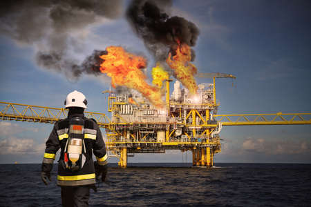 Photo pour Fire fighter on oil and gas industry, successful firefighter at work , Fire suit for fighter with fire and suit for protect fire fighter, Security team when fire case. restricted area or danger area. - image libre de droit