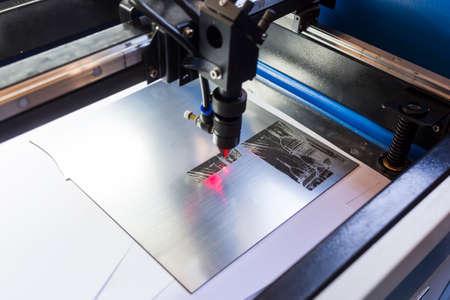 Laser machine is cutting an image on a flat sheet ot steel in a university laboratory.