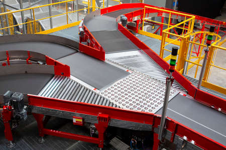 Foto de Empty conveyor sorting belt at distribution warehouse. Distribution hub for sorting packages and parcels delivered by air transportation. - Imagen libre de derechos