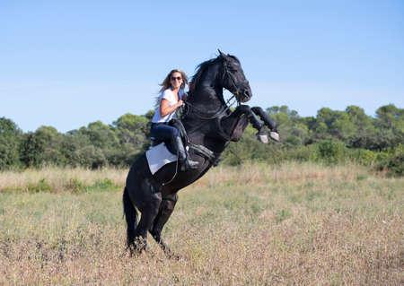 Photo pour riding girl are training her black horse - image libre de droit