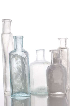 Antique bottles on white table  Professionally spotted and retouched.