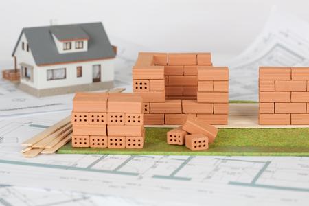 Foto de Model house construction with brick on blueprint - Imagen libre de derechos