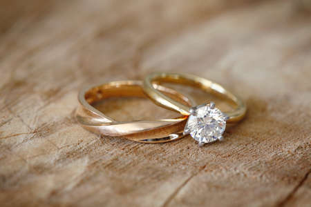 Photo pour Solitaire engagement diamond ring with wedding band on wooden organic background. - image libre de droit