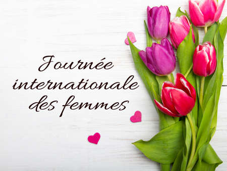 Women's day card with French words 'Journee internationale des femmes'. Tulip bouquet on white wooden background