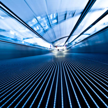 Moving blue travelator in office hall, square composition
