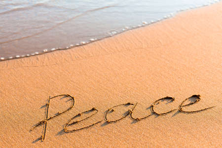 Word Peace on sand near sea wave