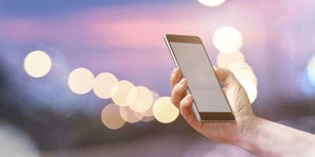 Photo pour Closeup female hand holding mobile smart phone over light bokeh - image libre de droit